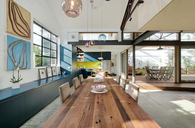 in-diesem-modernen-umgebauten-lager-verbindet-ein-neues-angehobenes-holzdeck-die-wohnbereiche-des-hauses-mit-dem-hof-glasschiebeturen-und-fenster-lassen-das-sonnenlicht-durch-den-innenraum-filtern