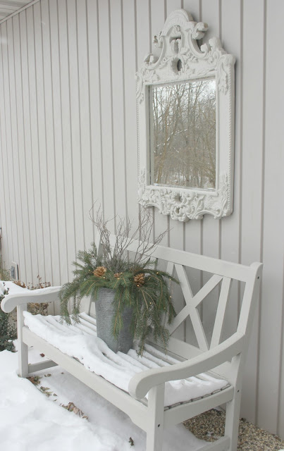 Snow covered bench with fresh greenery in courtyard decorated for Christmas