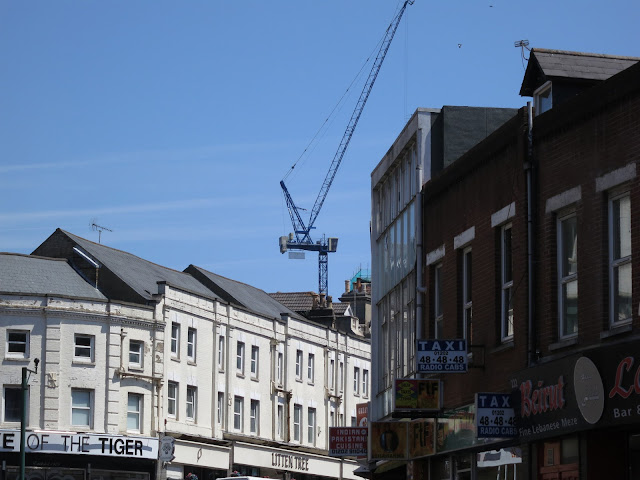 Crane against blue sky behind buildings in urban street.
