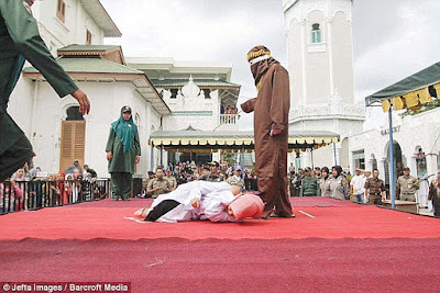 A muslim woman is caned in Banda Aceh, Indonesia, in October 2016.
