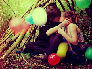 young-boy-kisses-cute-girl-lips-in-forest-wood-below-tress-image.jpg