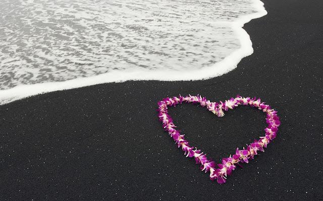 Roze liefdes hartje van bloemen op het strand