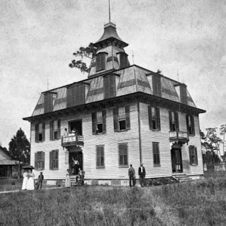 Black and white photo from late 1800s shows courthouse in Enterprise, FL, with people standing out front