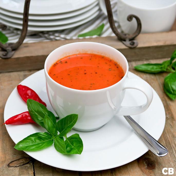 Koffiekopjes met een romige soep van geroosterde tomaten en paprika's