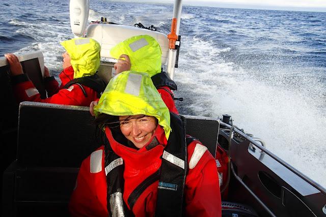Kolme henkeä pelastautumispuvuissa veneen kyydissä