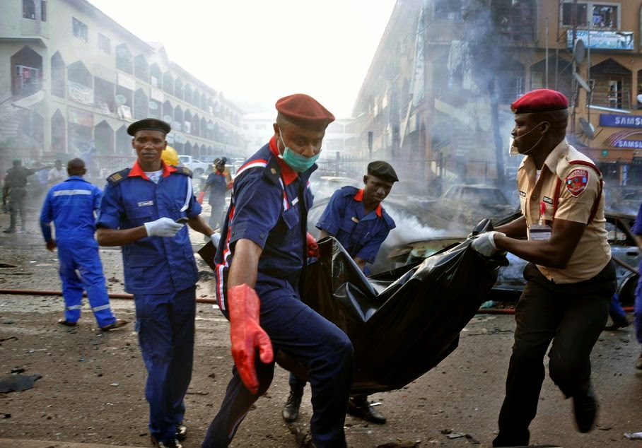 Rescue workers carry the remains of a person in a body bag after an explosion at a shopping mall in Abuja, Nigeria, Wednesday, June 25, 2014. Police said more than 20 people were killed and many wounded in the explosion.