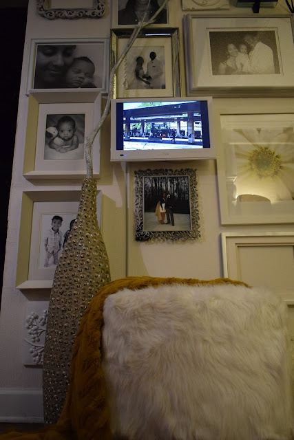 Family portrait wall, Chic white faux fur storage ottoman, Mirrored frames, black and white photos, White LED TV; By: JoFer Interior