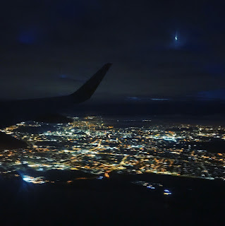 view from plane window at night with city light below