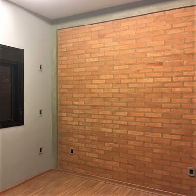 O escritório no pavimento térreo após, conclusão da obra, mostra a parede de tijolinhos aparentes que não são meros revestimentos e salientam as partes estruturais da edificação, como pilar e viga de concreto armado *.