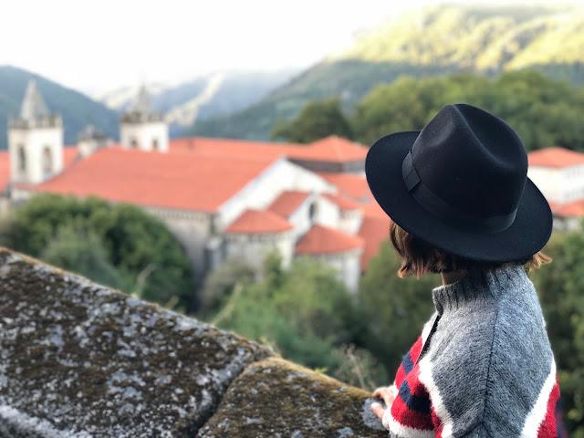 Mujer con sombrero mirando un monasterio