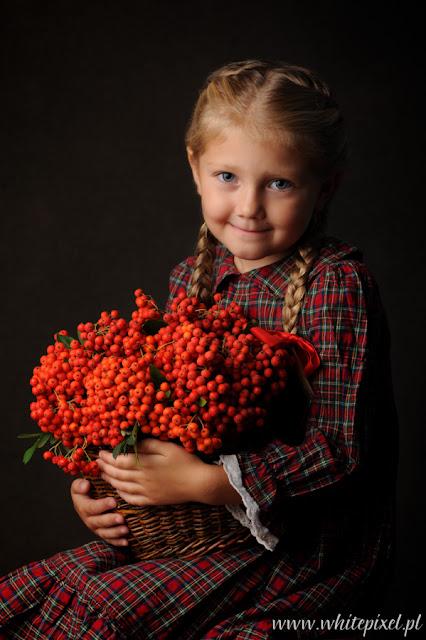 Stylizowana sesja studyjna dziecka w Lublinie, dziewczynka Julia w sukience trzyma kosz jarzębiny