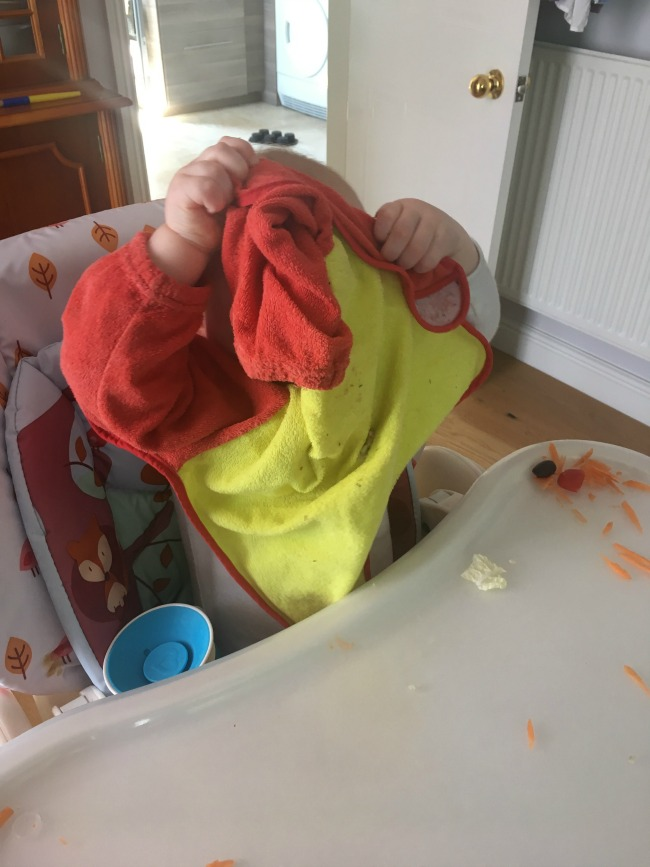 baby-taking-bib-off-and-playing-hide-and-seek