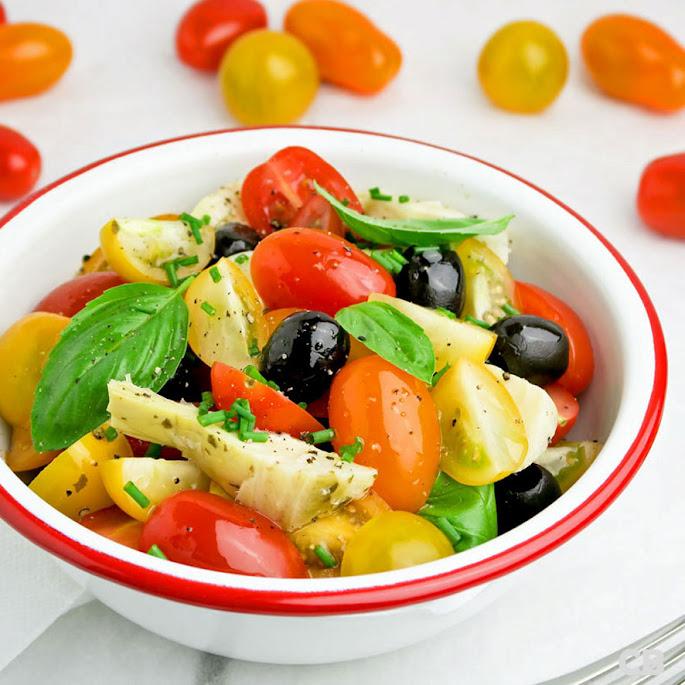 Salade van cherrytomaatjes, artisjokkenharten, zwarte olijven en verse kruiden