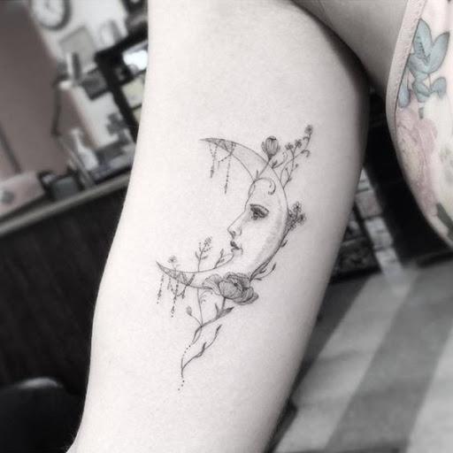 Uma personificação da lua crescente é adornado com flores, neste tatuagem prestados em que o portador da parte superior do braço.
