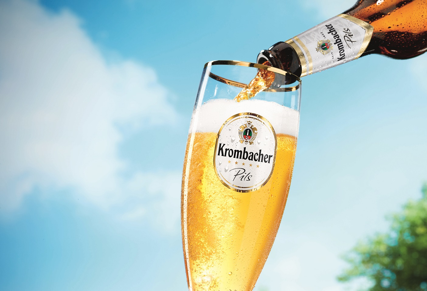 Krombacher Pils being poured into a tall glass