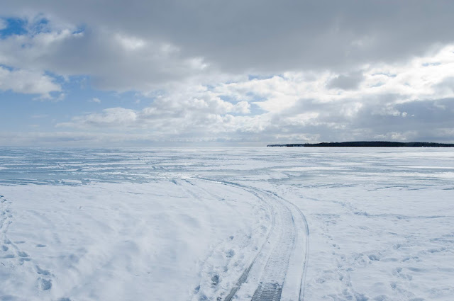 Snowmobiles trails left in thick snow cover on Lake Couchiching, Ontario.