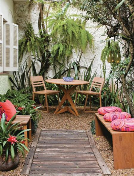 jardim estrito com móveis rústicos, com mesa, cadeiras e bancos