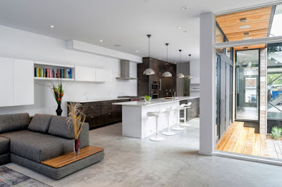 modern living area and open kitchen with breakfast bar and stools