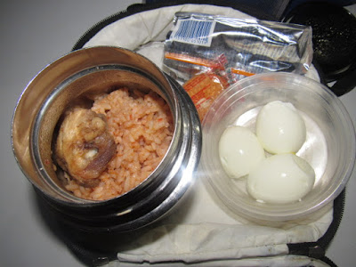 Nigerian school lunchbox meal of jollof rice with chicken and a side of boiled eggs