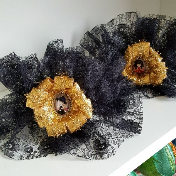 Finished pair of handmade black lace ankle cuffs sitting on white shelf
