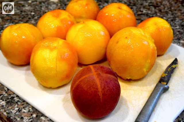 An unpeeled, blanched peach beside peaches that have been blanched and peeled