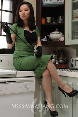 dominatrix in a green dress, holding a whip