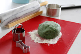 Counter top with ball of green dog treat dough on a red rolling mat, cookie cutters, and baking supplies