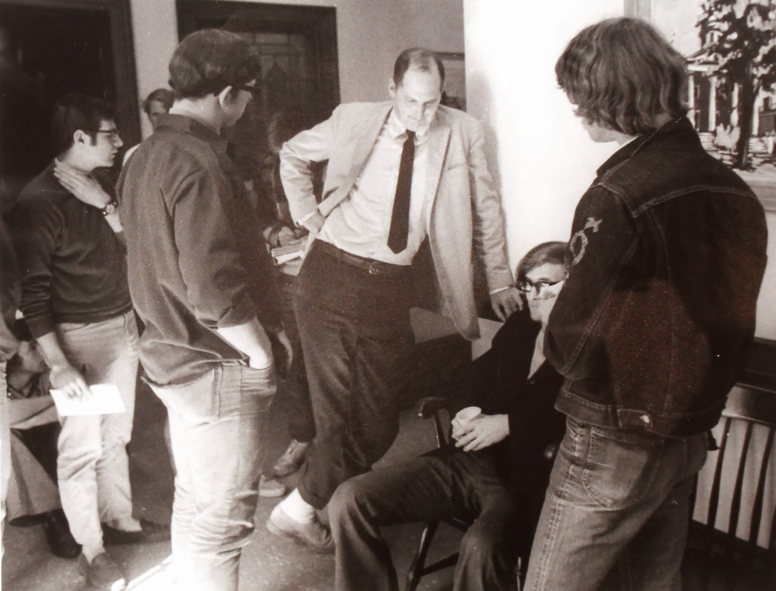 A black and white photograph of a small group of people talking.