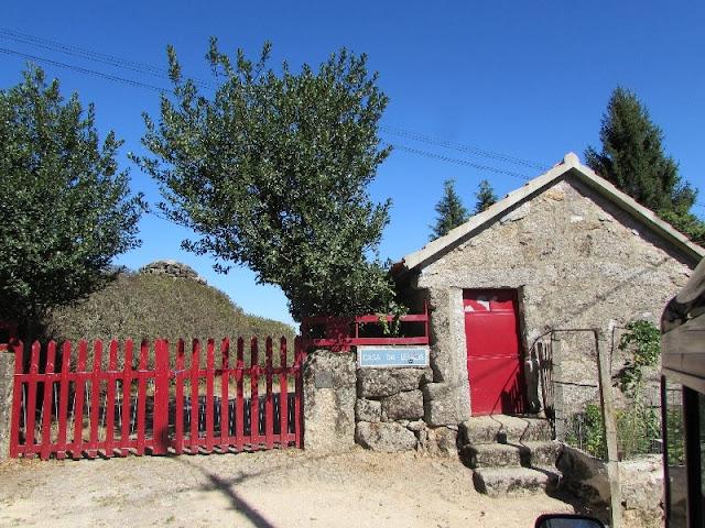 Casa em pedra com porta e portão vermelhos