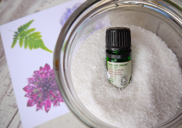 a bottle of peppermint essential oil lay in a glass jar of epsom salts