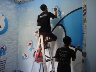 pelukis sedang menggambar kamar anak bertemakan doraemon