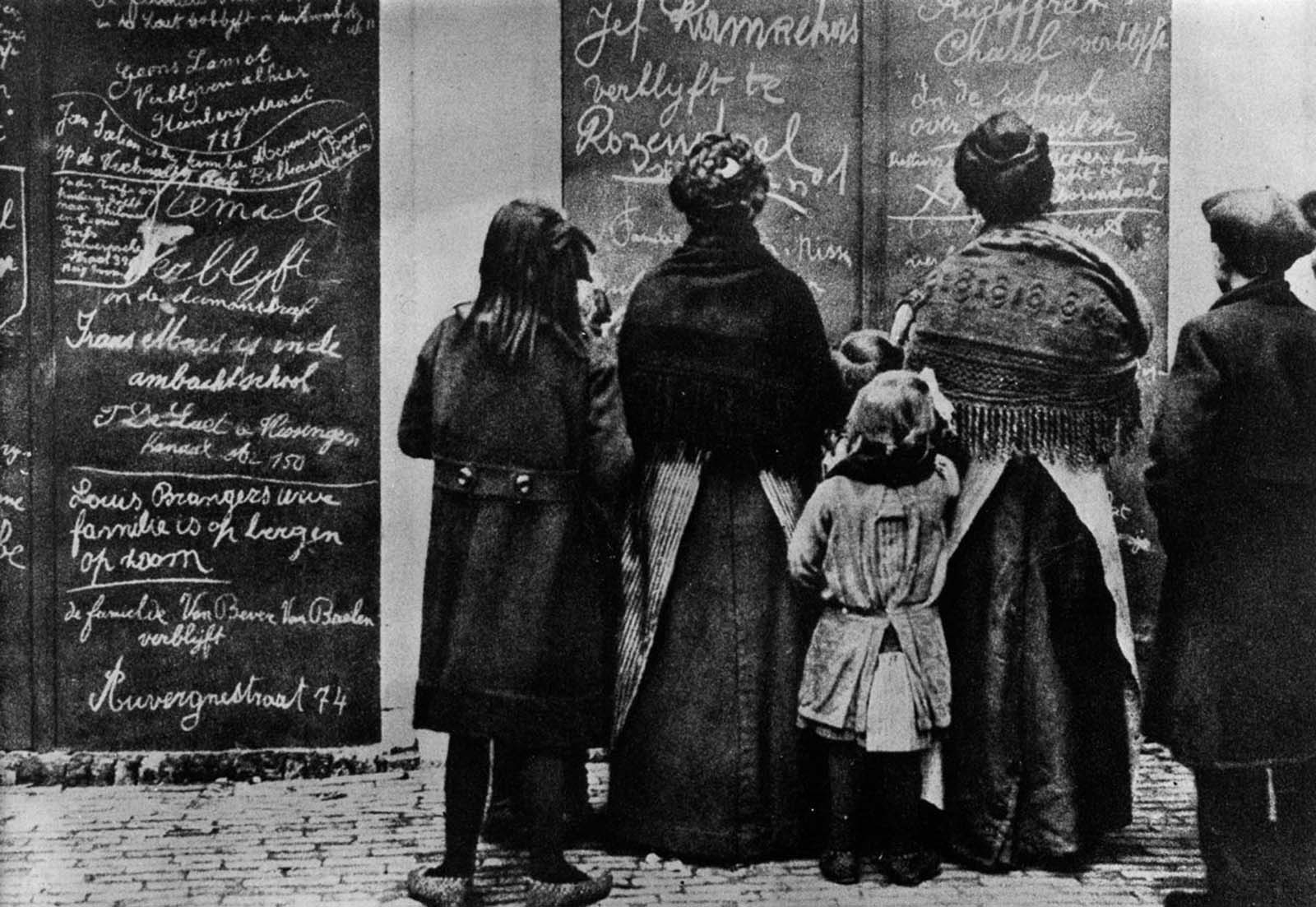 Belgian refugees read Flemish messages left by other refugees in a French town. 1915.