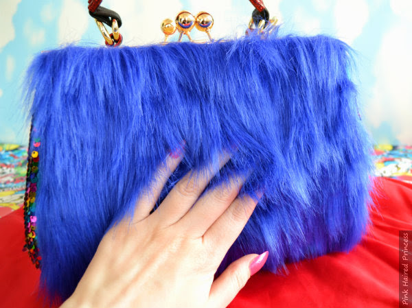 hand showing length of blue fur fabric used on Gonzo handbag
