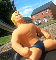 Stretch Armstrong seated on a swing