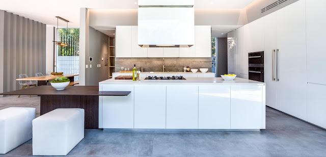 Cuisine moderne blanc brillant avec îlot, façades sans poignées et espace repas en bois
