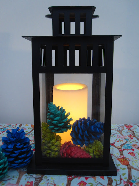 Painted pine cones in a black lantern with an led candle