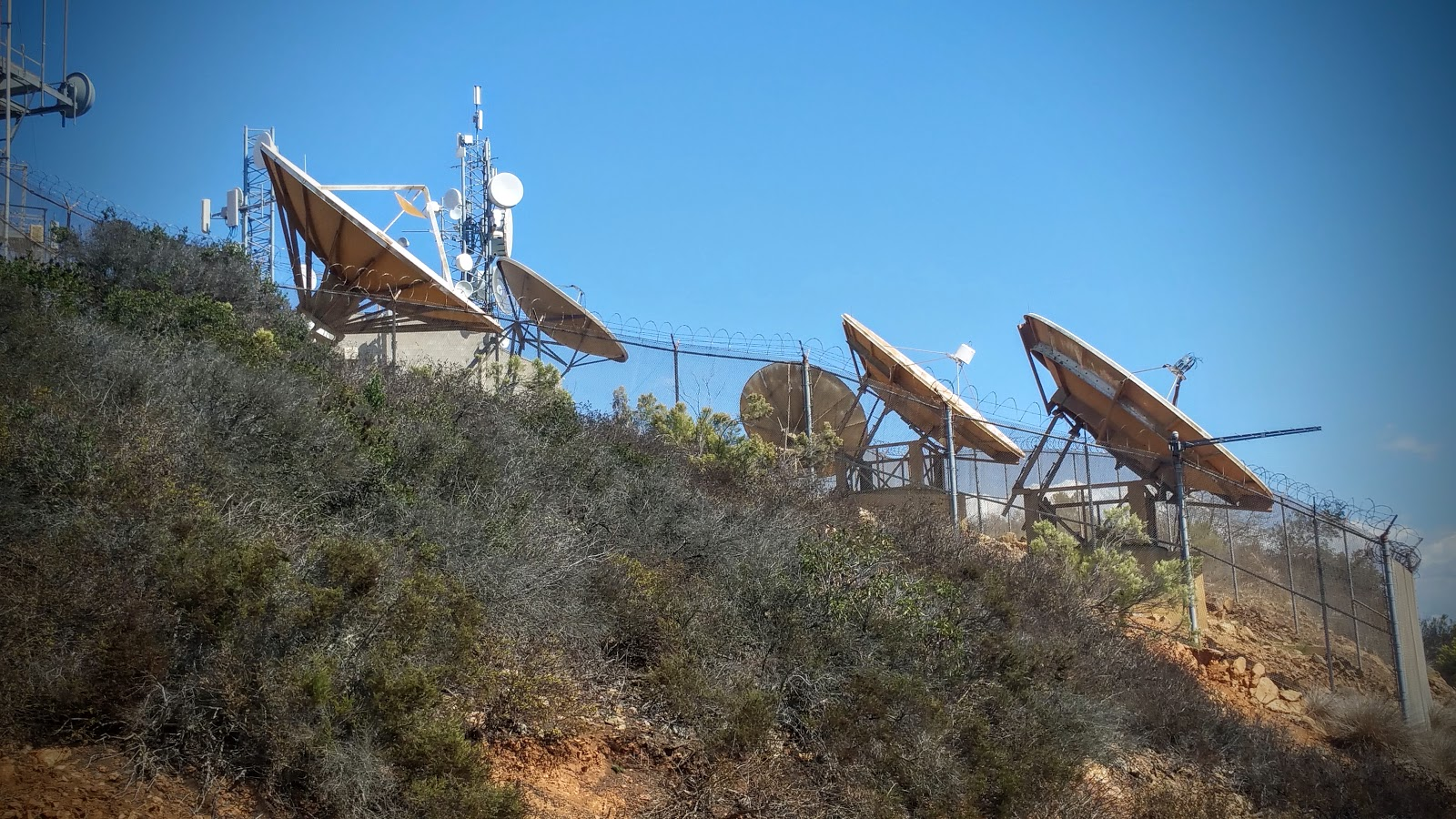 Barb wire surrounds two large satellies dishes.