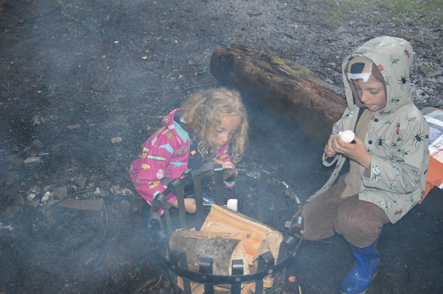 George and Molly toasting marshmallows over a fire.