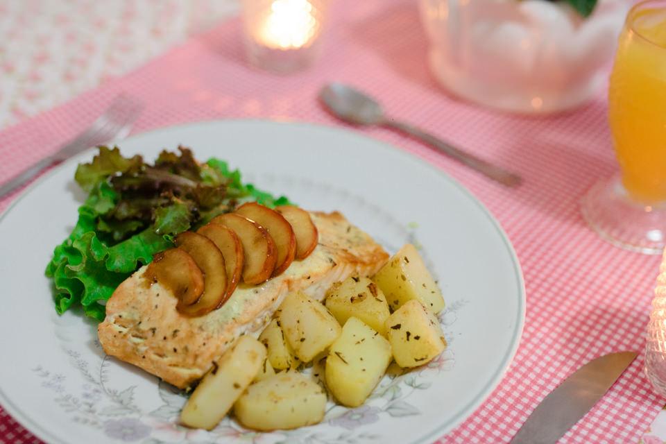 Foto do prato de Salmão grelhado acompanhado de batatas e molho de iogurte e ervas finas a luz de velas
