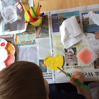 Child painting a flat clay chick