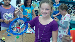 Girl student holding her finsihed dream catcher project.