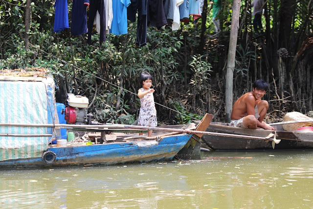 Cute little girl along the Mekong Delta, Vietnam - lifestyle and travel blog