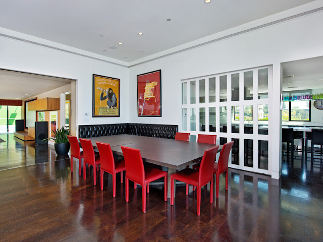 Photo of dining room interiors at the Bel Air modern residence with red chairs