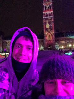Two people wearing warm winter clothing with the Parliament buildings behind them.