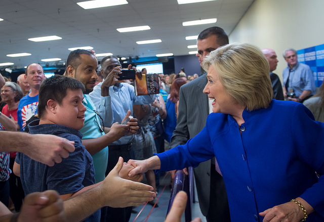 Hillary reaches into the crowd to shake the young man's hand; she has a huge grin and he is looking back at her in awe