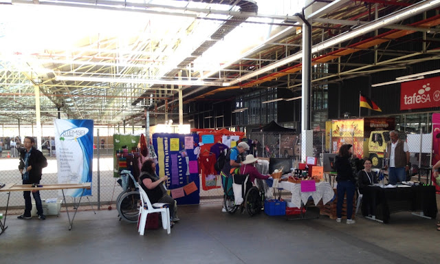 A wide view of the Lupey Loops exhibit. Stemsel Club is to the left and Youth Space is on the right. The Lupey Loops exhibit has items pinned to the back wall (which is a mesh fence covered with fabric). The left side is a row of chairs facing the centre of the space. The right side is bordered by a rectangular trestle table with display items facing the centre space in the middle.  There is a lot of space within the exhibit area for people to enter and to give a wheelchair room to move.