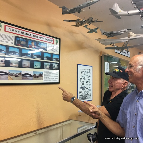 "docents C.J.and Andy Werback point to display re. ""It's a Mad, Mad, Mad, Mad World"" at Pacific Coast Air Museum in Santa Rosa, California"
