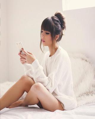 pose sentada en la cama mirando el movil