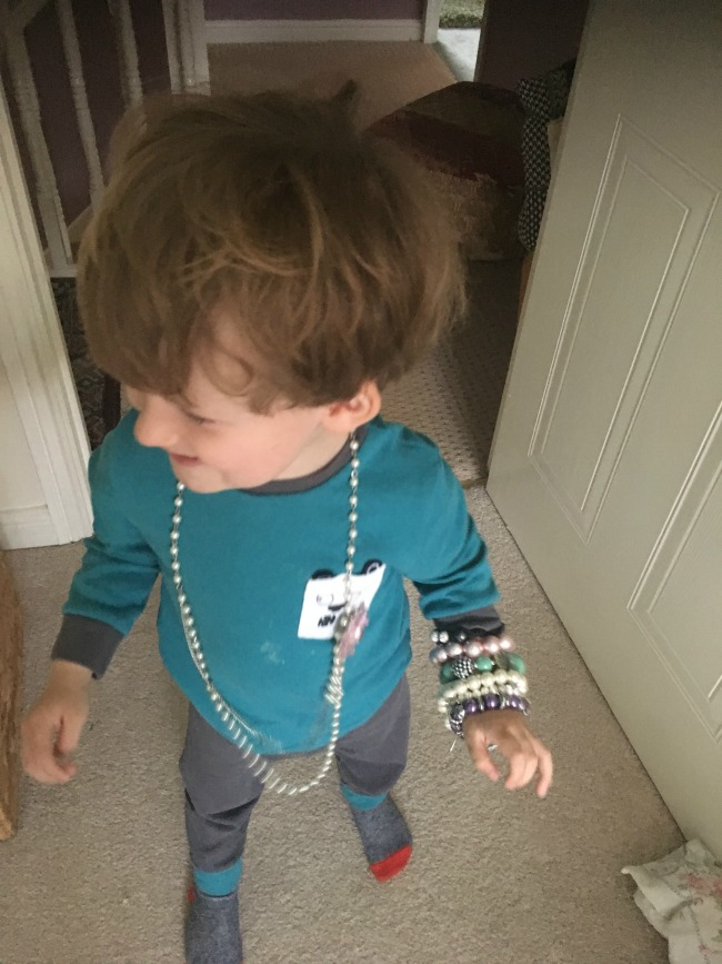 toddler-laughing-and-wearing-bracelets-and-a-necklace