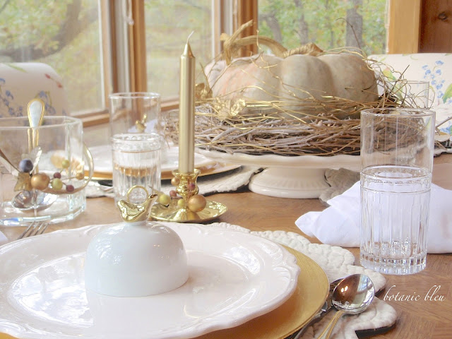 Thanksgiving gold and white table has a cinderella pumpkin with gold and white wreath base